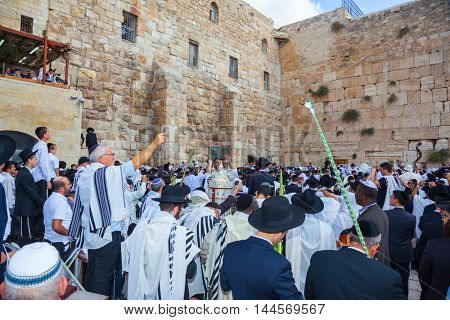 JERUSALEM, ISRAEL - OCTOBER 12, 2014:  The Jews of tallit hold four ritual plants. Morning autumn Sukkot, Blessing of the Kohanim. The area in front of Western Wall of Temple filled with people