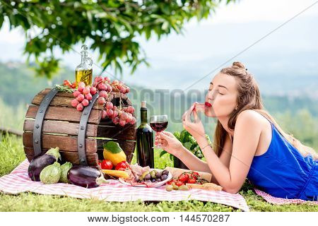 Beautiful woman tasting prosciutto lying on the grass with lots of tasty italian food and wine in the countryside in Tuscany.