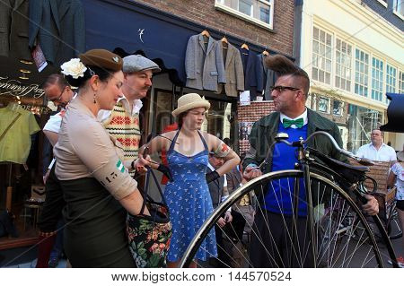 AMSTERDAM, NETHERLANDS - MAY 8, 2016: Unidentified people in vintage style clothes with their bicycles on Tweed Ride, Amsterdam, Netherlands. This event is dedicated to the style of old England.