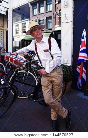 AMSTERDAM, NETHERLANDS - MAY 8, 2016: Unidentified man in vintage style clothes with bicycle on Tweed Ride Amsterdam Netherlands. This event is dedicated to the style of old England.