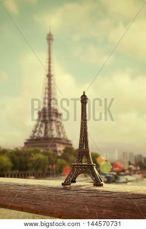 Eiffel Tower Paris France. Eiffel Tower souvenir in front of real tower. Retro filter effect.
