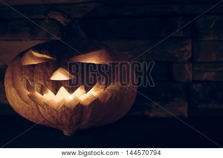 Jack O' lantern with luminous devil smile for halloween in darkness on stone background with copy space
