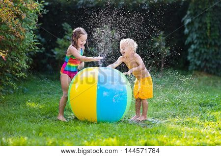 Child playing with toy ball garden sprinkler. Preschooler kid run and jump. Summer outdoor water fun in the backyard. Children play with hose watering flowers. Kids splash on sunny day.