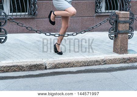 Female feet in shoes with heels jump over the fence in the form of a chain close-up