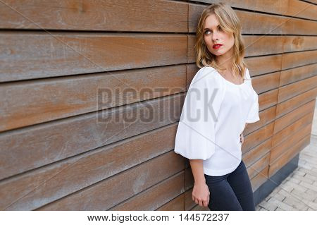 Portrait of beautiful blonde young woman leaning on wall boards and looking to the side