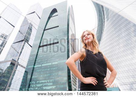 smiling girl in black dress near high building