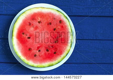 Round watermelon slice in plate on dark blue wooden background top view