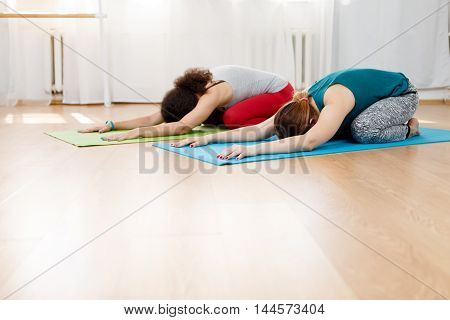 Two young women practicing yoga asana on floor outdoors sitting in forward bend posture