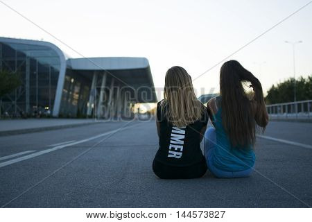 Two girls sit on the road looking at the sunset