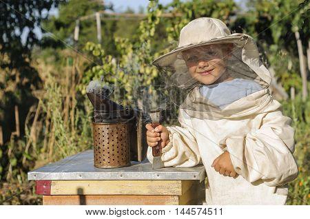 Portrait of a cheerful little boy beekeeper.
