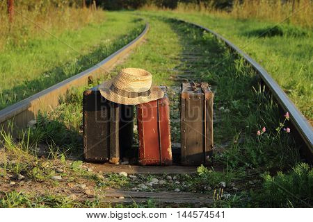old suitcases and hat on the train tracks