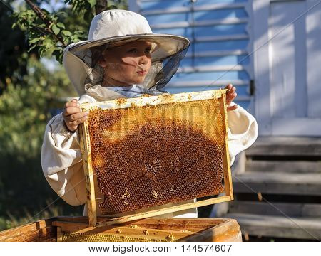 Young beekeeper boy holding frame of honeycomb.