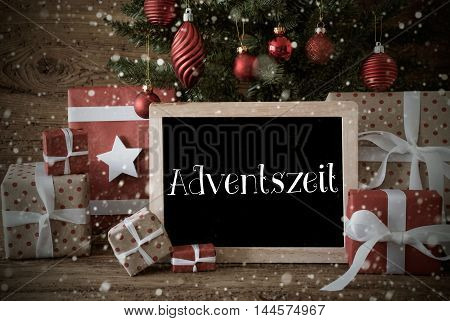 Nostalgic Christmas Card For Seasons Greetings. Christmas Tree With Balls And Snowflakes. Gifts In The Front Of Wooden Background. Chalkboard With German Text Adventszeit Means Advent Season