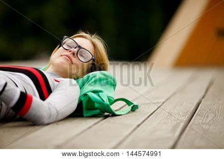 dreamy girl spectacled lies on wooden roof