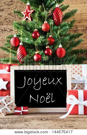 Colorful Christmas Card For Seasons Greetings. Christmas Tree With Balls. Gifts Or Presents In The Front Of Wooden Background. Chalkboard With French Text Joyeux Noel Means Merry Christmas