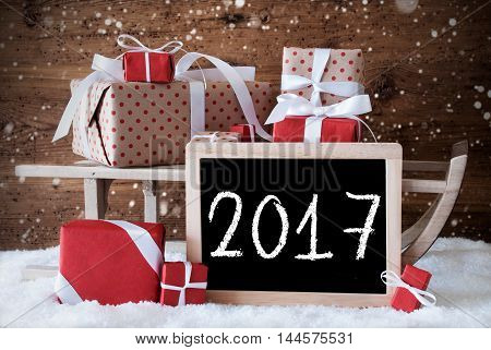 Sled With Christmas And Winter Decoration And Snowflakes. Gifts And Presents On Snow With Wooden Background. Chalkboard With English Text 2017 For Happy New Year