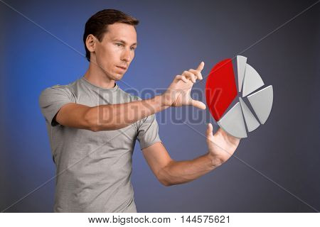 Man in t-shirt working with pie chart on blue background.