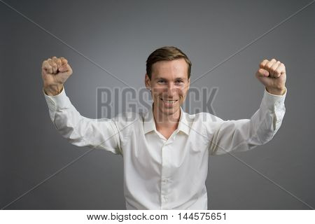 Gesture of success. Smiling man in white shirt with raised hands.