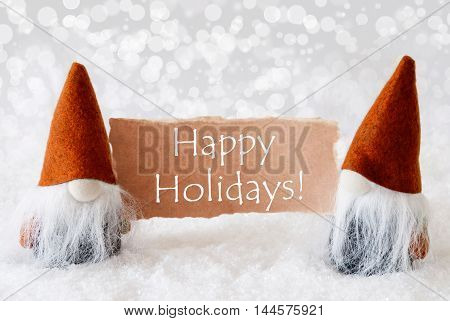 Christmas Greeting Card With Two Bronze Gnomes. Sparkling Bokeh Background With Snow. English Text Happy Holidays