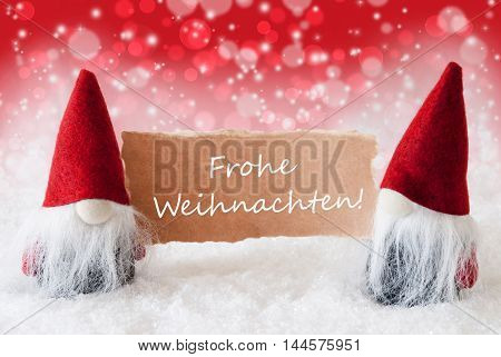 Christmas Greeting Card With Two Red Gnomes. Sparkling Bokeh And Christmassy Background With Snow. German Text Frohe Weihnachten Means Merry Christmas