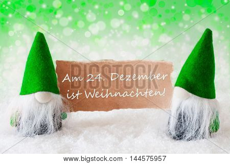 Christmas Greeting Card With Two Green Gnomes. Sparkling Bokeh And Natural Background With Snow. German Text Weihnachten Means Christmas