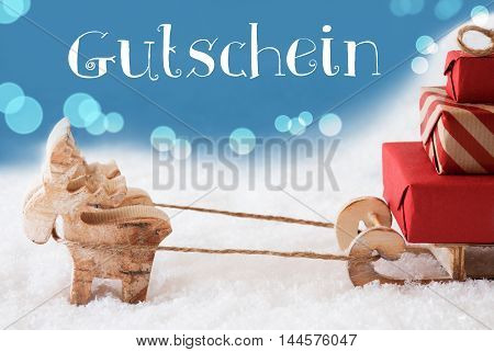 Moose Is Drawing A Sled With Red Gifts Or Presents In Snow. Christmas Card For Seasons Greetings. Light Blue Background With Bokeh Effect. German Text Gutschein Means Voucher