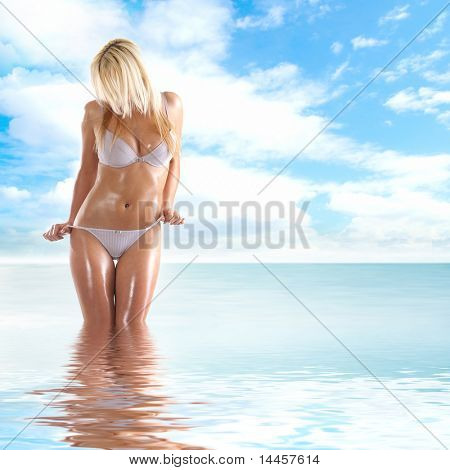 Sexy body of young attractive lady over natural background of sea and sky
