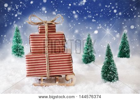 Sleigh With Christmas Gifts Or Presents. Snowy Scenery With Snow And Trees. Blue Background With Snowflakes And Sparkling Stars