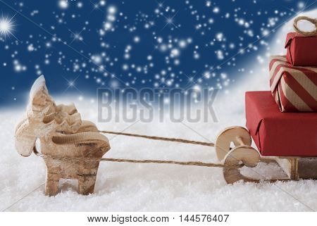 Moose Is Drawing A Sled With Red Gifts Or Presents In Snow. Christmas Card For Seasons Greetings. Blue Background With Bokeh Effect And Snowflakes. Copy Space For Advertisement