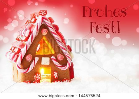 Gingerbread House In Snowy Scenery As Christmas Decoration. Candlelight For Romantic Atmosphere. Red Background With Bokeh Effect. German Text Frohes Fest Means Merry Christmas