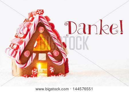 Gingerbread House In Snowy Scenery As Christmas Decoration With White Background. Candlelight For Romantic Atmosphere. German Text Danke Means Thank You
