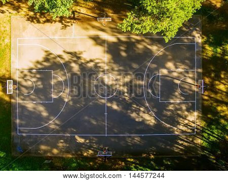 Flat lay, aerial top view of outdoor basketball court in the forest