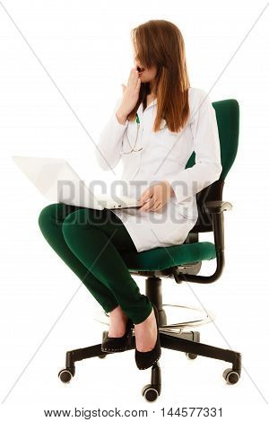 Medicine. Full length of tired sleepy overworked woman doctor in lab coat working on computer laptop and yawning isolated.
