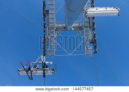 Ski lift with seats going over the mountain and paths from skies and snowboards