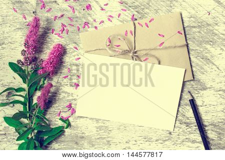 Blank white greeting card envelope and pencil with purple wildflowers on white rustic wood background with petals around. vintage toning