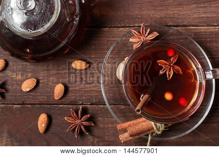 Autumn hot tea with spices and berries in glass cup and teapot on wooden background. top view