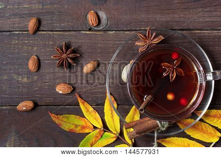 Autumn hot tea with spices and berries in glass cup on wooden background with autumn leaves. top view
