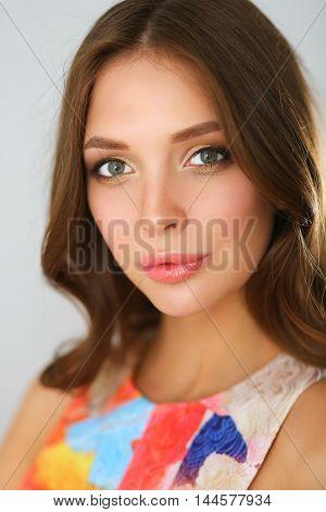 Beautiful female in sundress posing on white background.