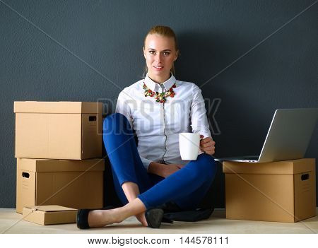 Woman sitting on the floor near a boxes with laptop .