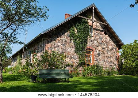 Facade wall of traditional Latvian house and green wooden bench