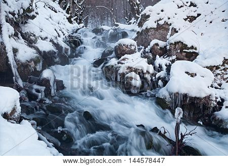 Water in frozen stream. Snowy river in forest in the winter. Long exposure