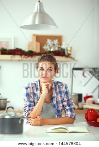 Woman reading magazine In kitchen at home