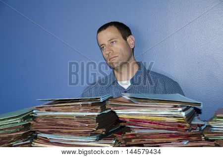 Man spacing out at work in front of a pile of files due to stress.