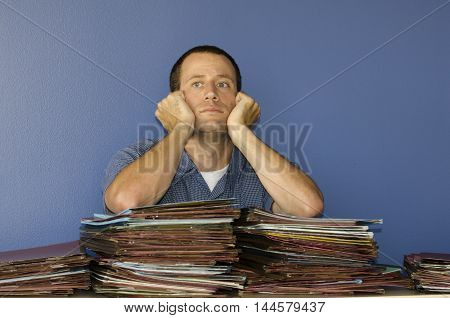 Office job stress. Stressed out at the office with piles of files to review.