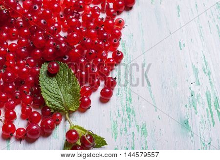 Ripe red currant with leaves on a wooden background.