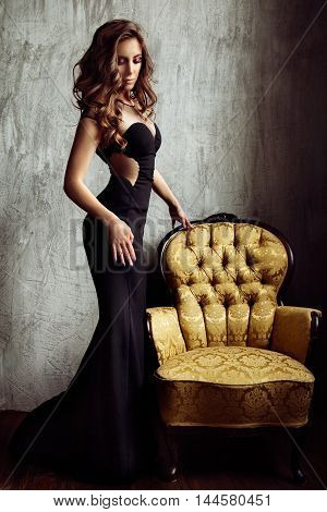 Portrait of elegant young brunette woman in black long evening dress in interior
