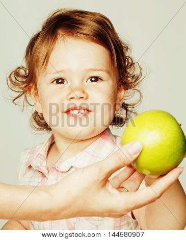 little cute baby girl pointing isolated on white close up with green apple smiling adorable