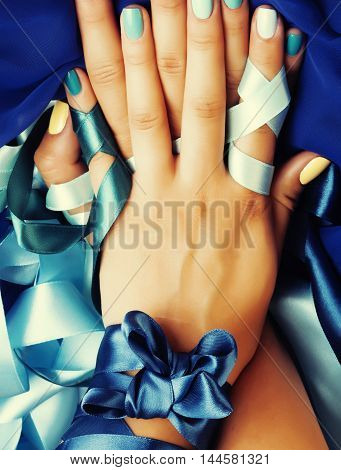 manicure with ribbon close up as a gift, blue colored
