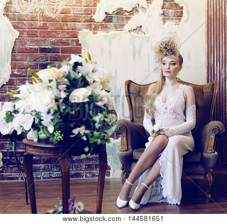 bright retro bride in luxury interiors with elegant hairstyle and flowers alone