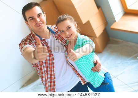 Young couple happy in their new modern design house showing thumbs up